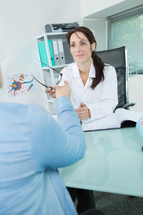 女性对顾客的眼镜师提供的玻璃框架 免版税库存照片