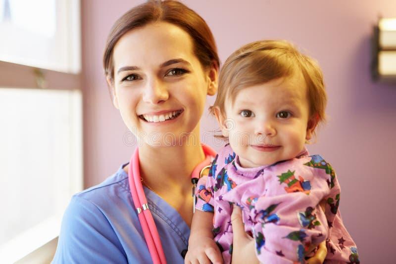 女性小儿科护士举行的女孩 免版税图库摄影