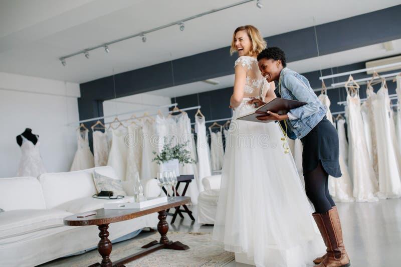 女性尝试在有妇女的婚礼服辅助在商店 免版税库存图片