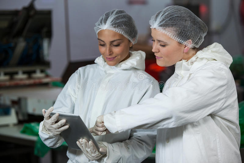 女性屠户谈论在数字式片剂 免版税库存图片