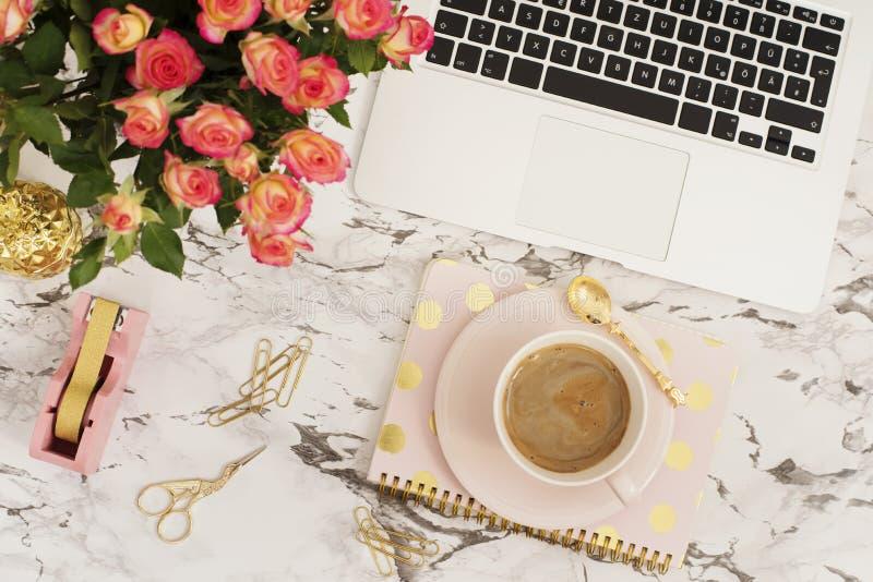 女性工作场所概念 在舱内甲板的自由职业者的工作区放置与膝上型计算机、咖啡、花、金黄菠萝、笔记本和pap的样式 免版税图库摄影