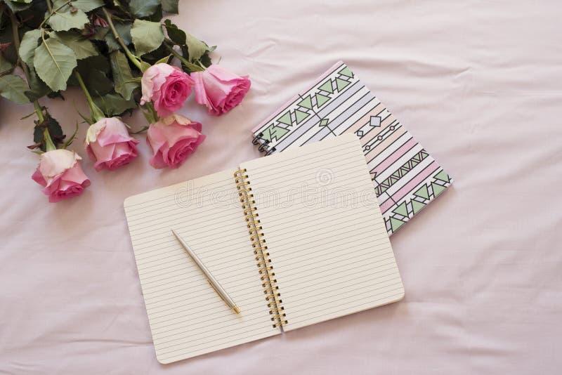 女性工作场所概念 自由职业者的在舱内甲板的时尚舒适的阴物工作区放置与开放笔记本,桃红色玫瑰flo的样式 库存照片
