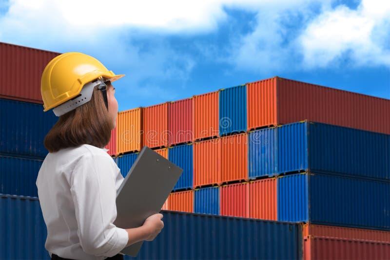女性工程师佩带的安全帽检查在运输的货物 免版税库存图片