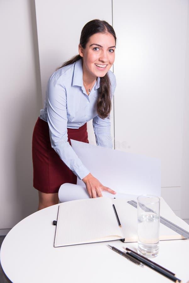 年轻女性工程师微笑着入照相机 免版税库存图片
