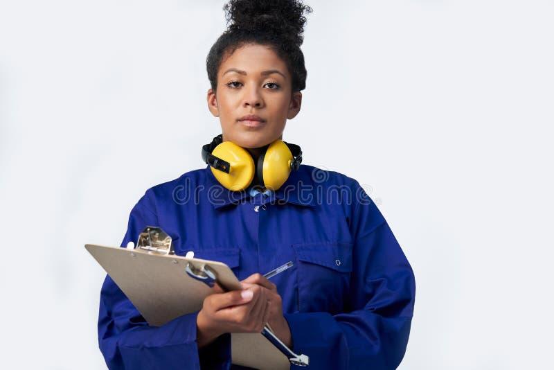女性工程师演播室射击画象有剪贴板和扳手的反对白色背景 免版税库存图片