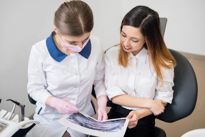 女性年轻牙医谈话与牙齿诊所的,审查的X-射线图象女性患者 牙科 免版税库存图片
