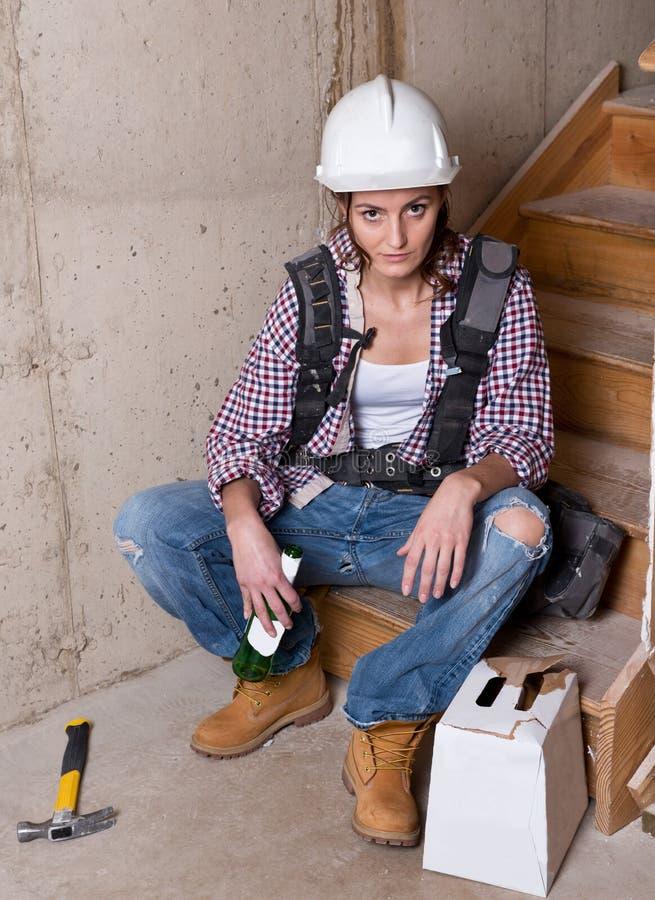 女性建筑工人饮用的啤酒 免版税图库摄影