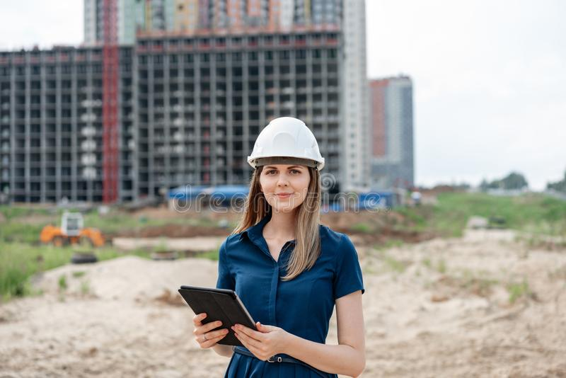 女性建筑工程师 有一台片剂计算机的建筑师在工地工作 年轻女人神色秘密审议 免版税图库摄影