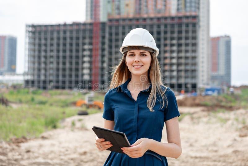 女性建筑工程师 有一台片剂计算机的建筑师在工地工作 年轻女人神色秘密审议 免版税库存照片