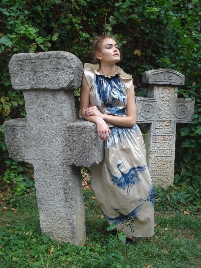 女性式样倾斜在传统石十字架 库存照片