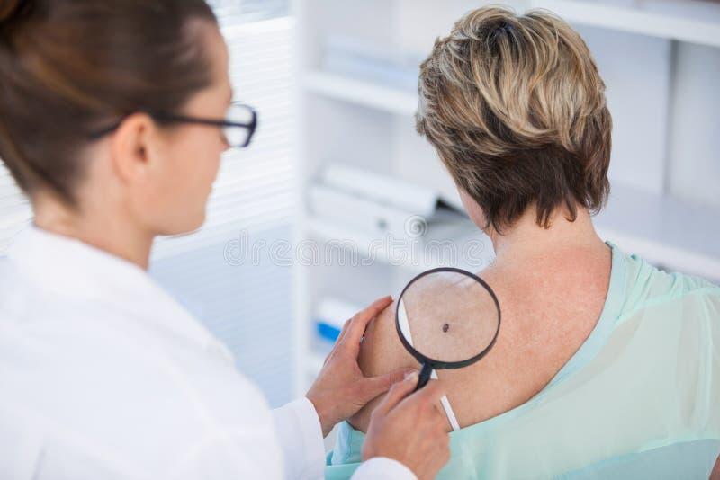 女性患者皮肤病学家审查的痣有放大镜的 免版税库存图片