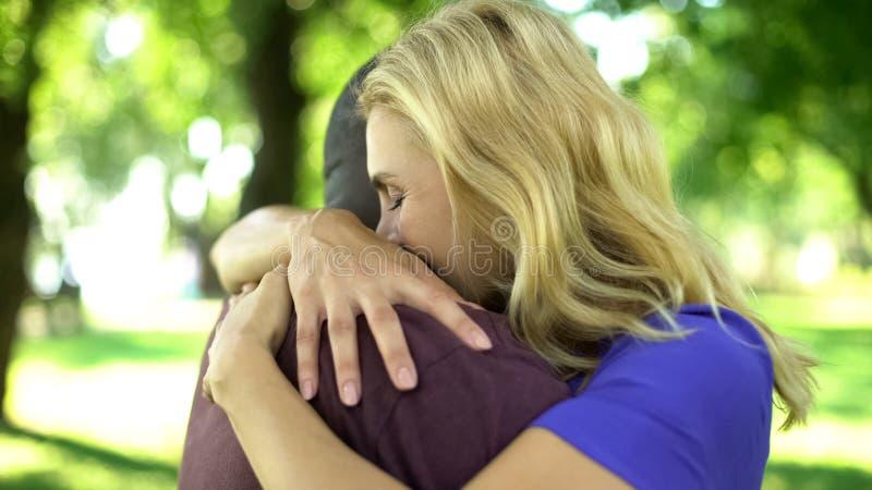 女性情感地拥抱人种间男朋友,持久恋爱 库存照片