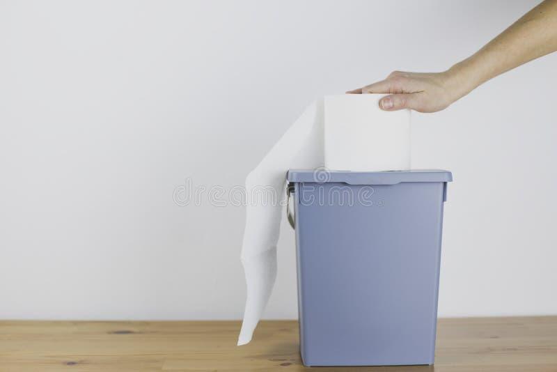 女性手为手纸到达,在容器站立 免版税库存照片