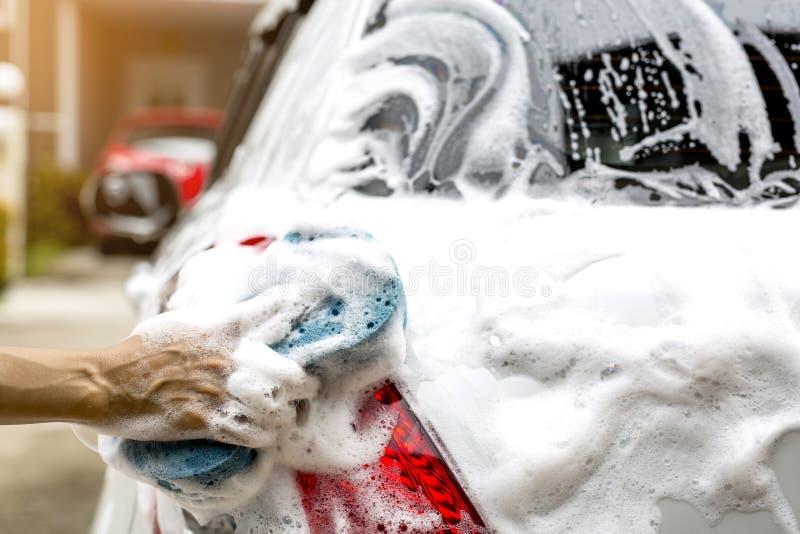 女性手举行与蓝色海绵洗涤的汽车 图库摄影