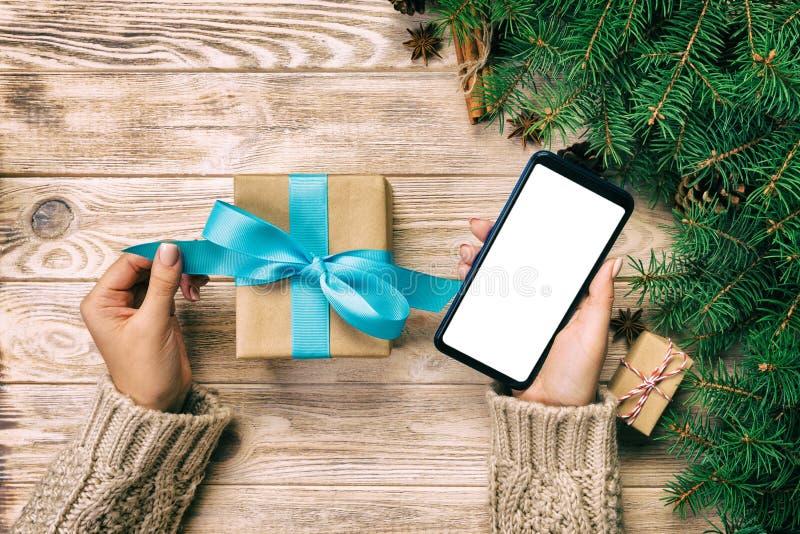 女性手举行包裹圣诞礼物箱子和读书按摩在电话有最高荣誉的在棕色木葡萄酒桌上 上面竞争 免版税库存照片
