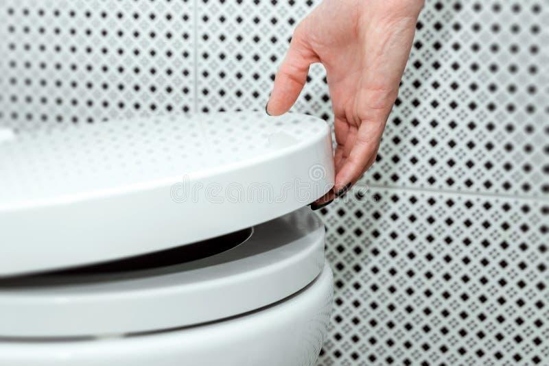 女性手举马桶,特写镜头的盒盖 个人卫生的概念 图库摄影