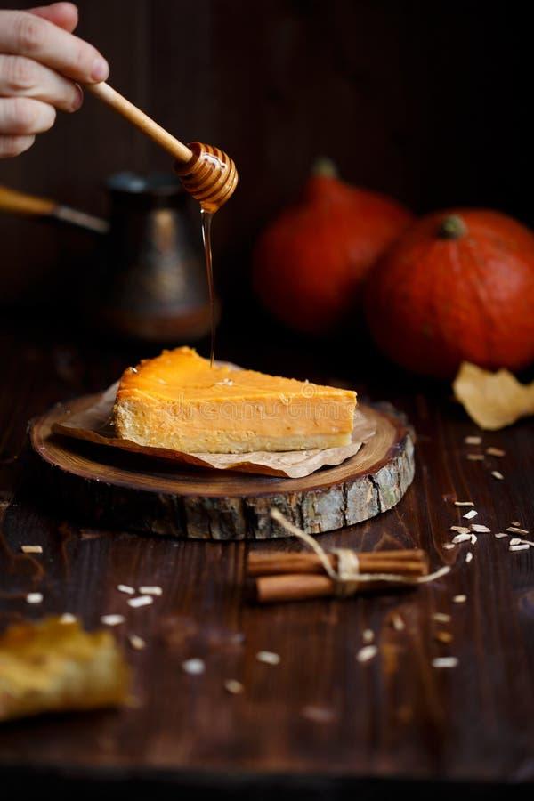 女性手倒蜂蜜南瓜乳酪蛋糕 南瓜,咖啡,叶子,在木黑暗的背景的香草 秋天和 免版税库存照片