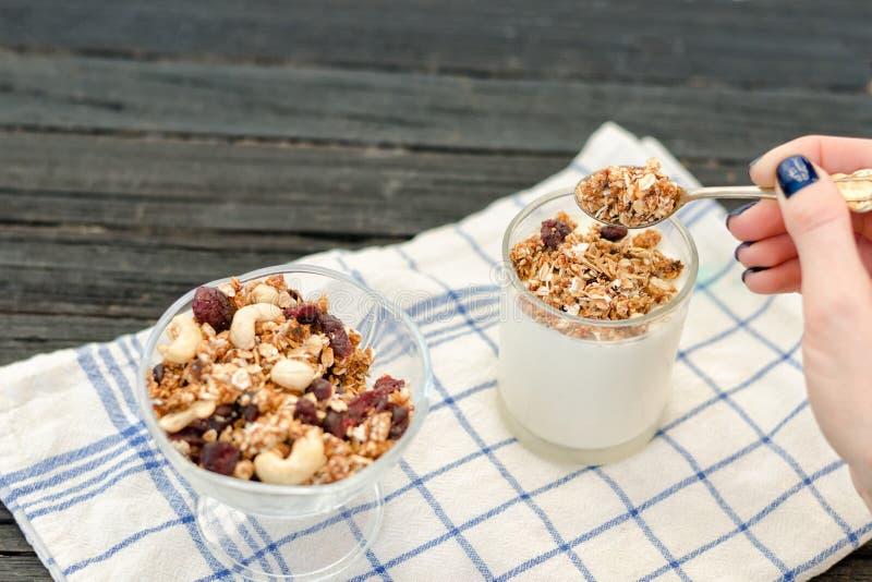 女性手倒酸奶格兰诺拉麦片 传统美国的早餐 图库摄影