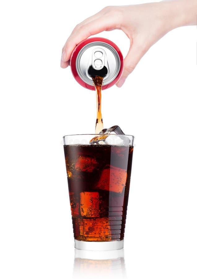 女性手倾吐的可乐饮料从锡到玻璃 免版税库存图片