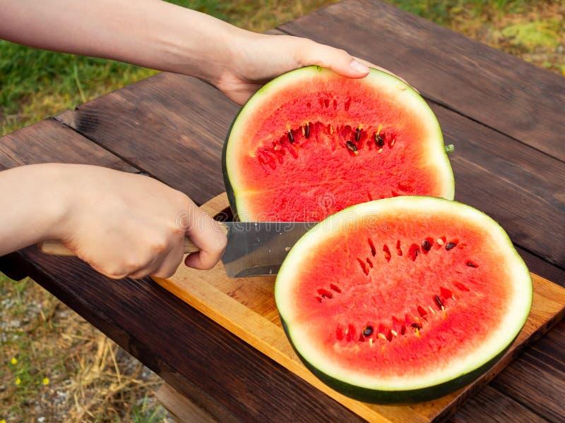女性手切了在一张木桌上的一个成熟西瓜与刀子 免版税库存图片