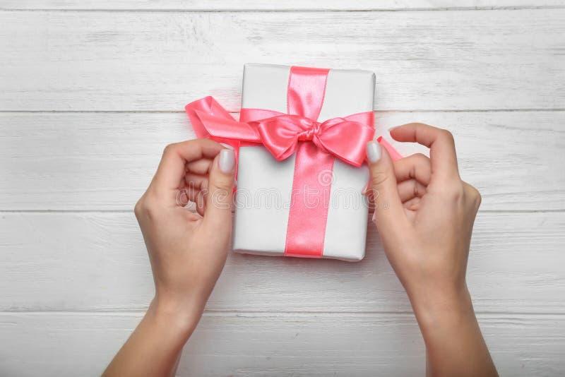 女性手和礼物盒有桃红色丝带的在白色木背景,顶视图 免版税库存图片