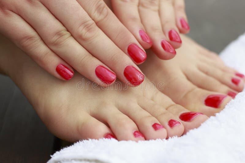 女性手和脚与一红色修指甲和修脚在木背景 免版税库存照片