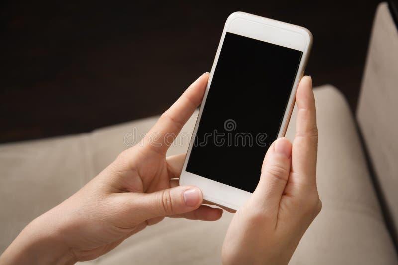 女性手在他们的手上拿着白色电话 手机特写镜头 库存照片