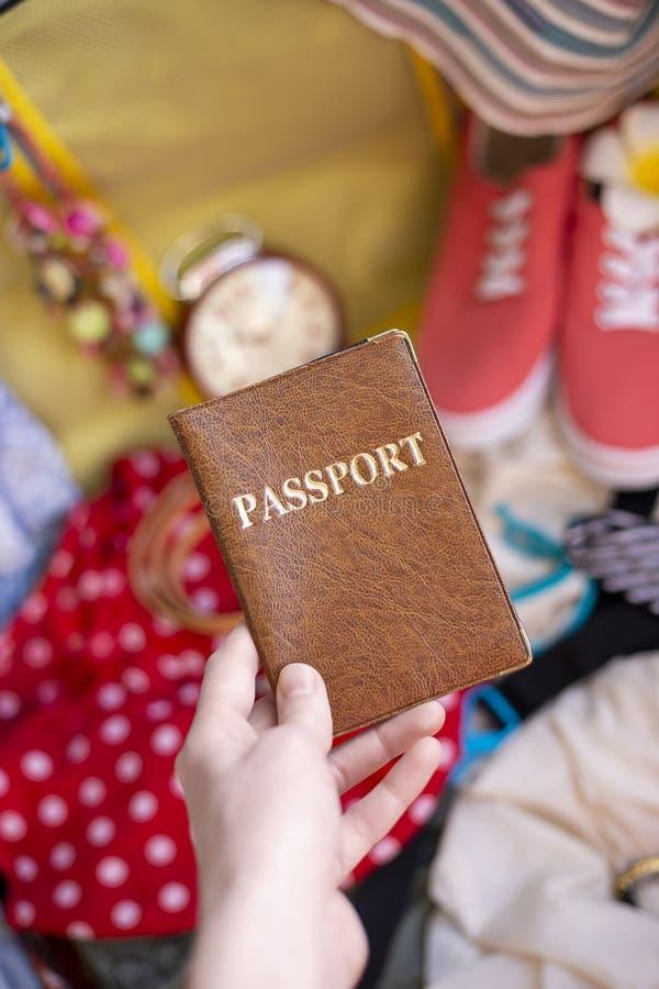 女性手在手提箱投入护照 免版税库存图片