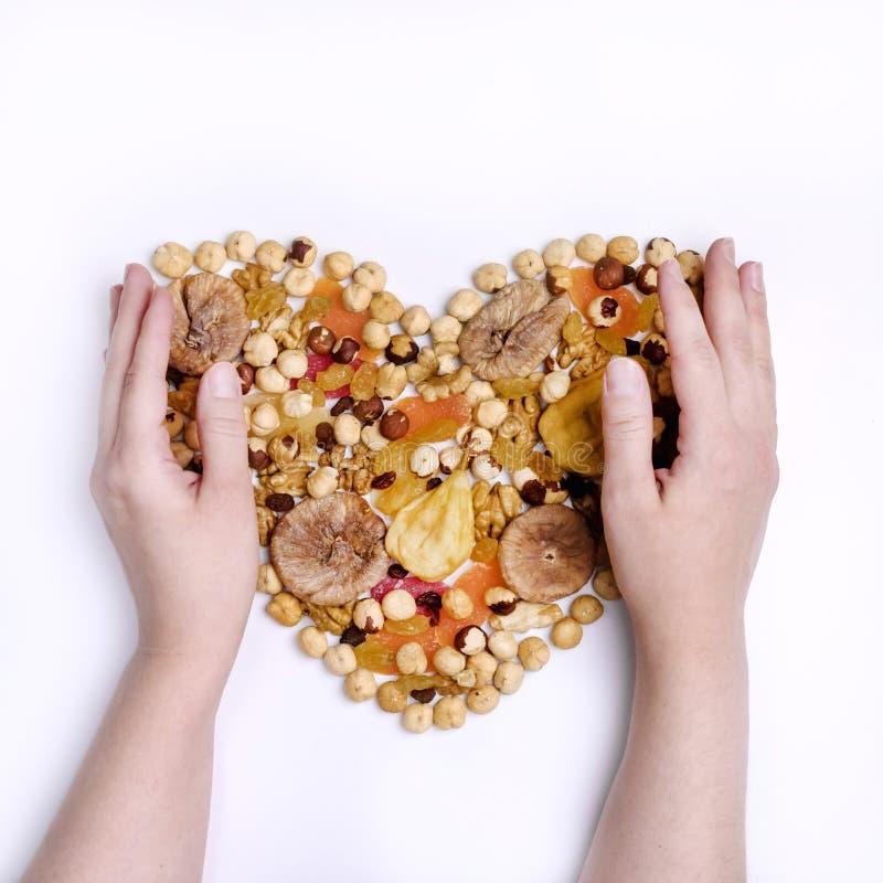 女性手坚果混合和干果子在心脏形状在白色背景顶视图正方形 免版税图库摄影