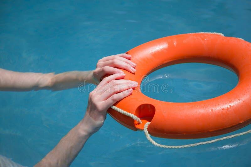 女性手对负lifebuoy在海洋 免版税库存照片