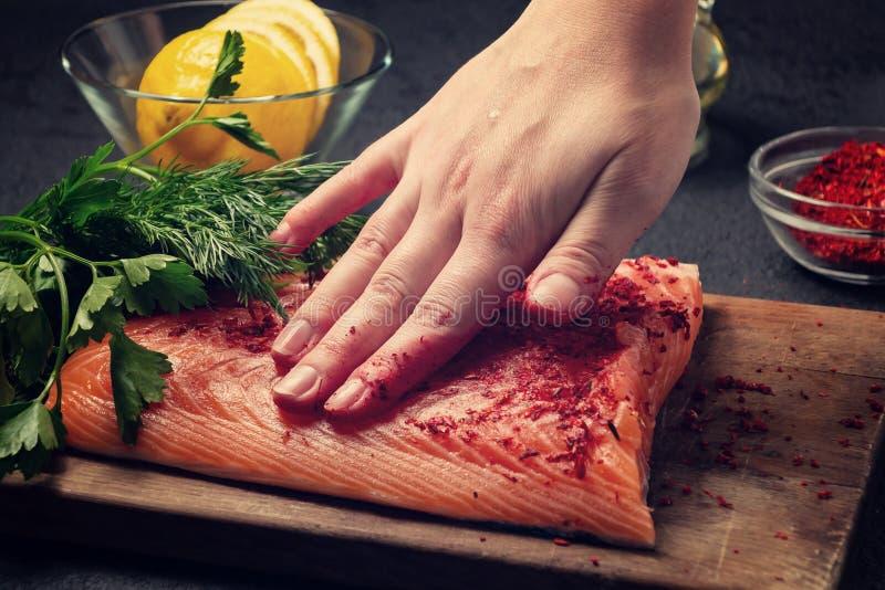 女性手抹上说谎在一个木切板与香料-照片,图象的三文鱼内圆角片断 免版税库存照片