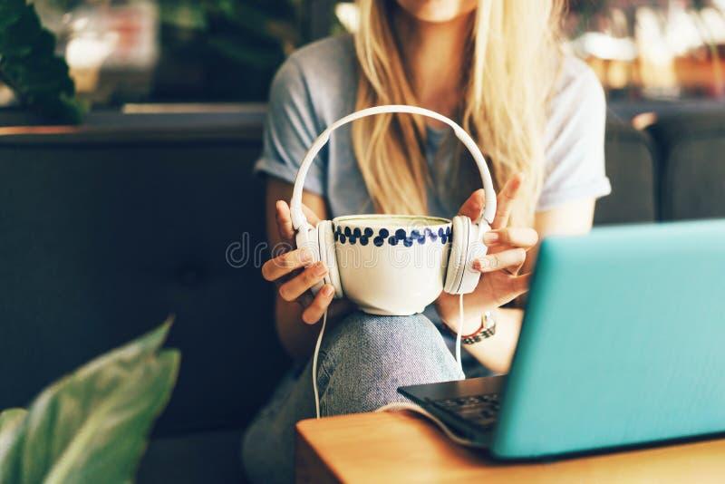 女性手拿着一个大杯子在大白色耳机的茶比赛 免版税库存照片