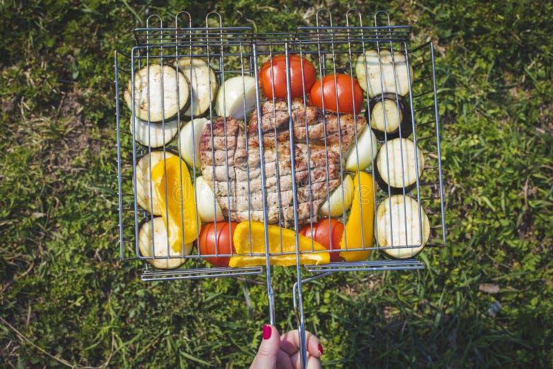 女性手拿着一个格栅的一个格子用猪肉牛排和新鲜蔬菜 库存照片