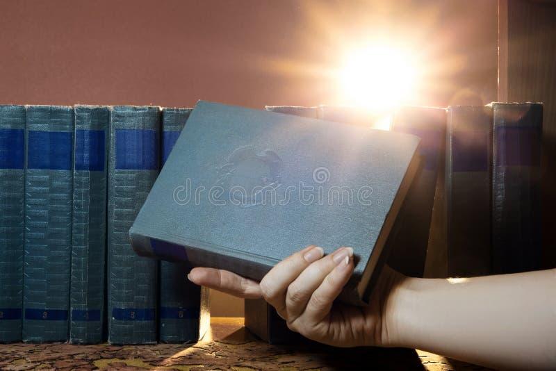 女性手拿着一本书,采取在架子的一本书 知识光  对知识的追求 免版税库存图片