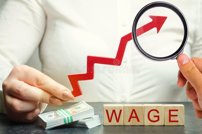 女性手拿着上面词薪水的箭头 薪金,工资率增量  促进,事业成长 提高标准  免版税库存照片