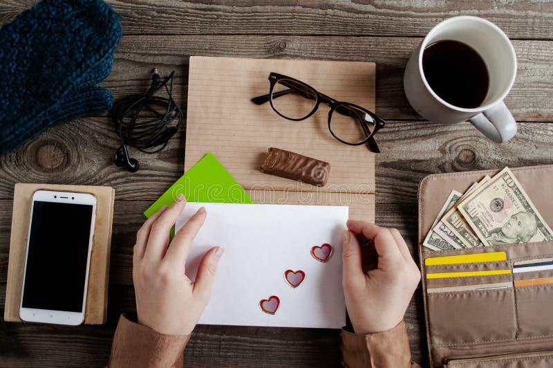女性手拿着与心脏的一个被密封的白色信封 免版税库存照片