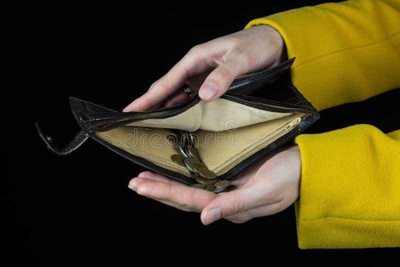 女性手拿着倾吐硬币的一个钱包,黑背景财务 库存图片