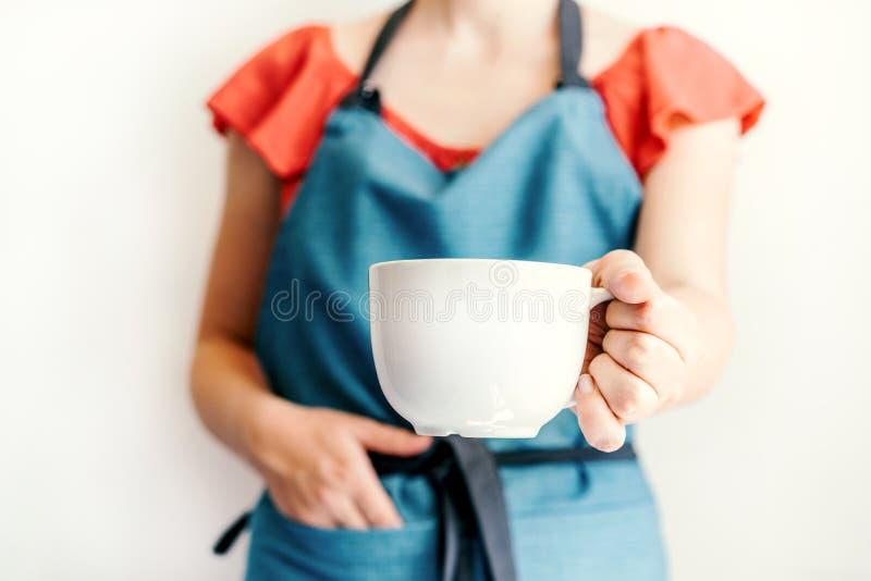 女性手拿着并且舒展一个大白色杯子 图库摄影