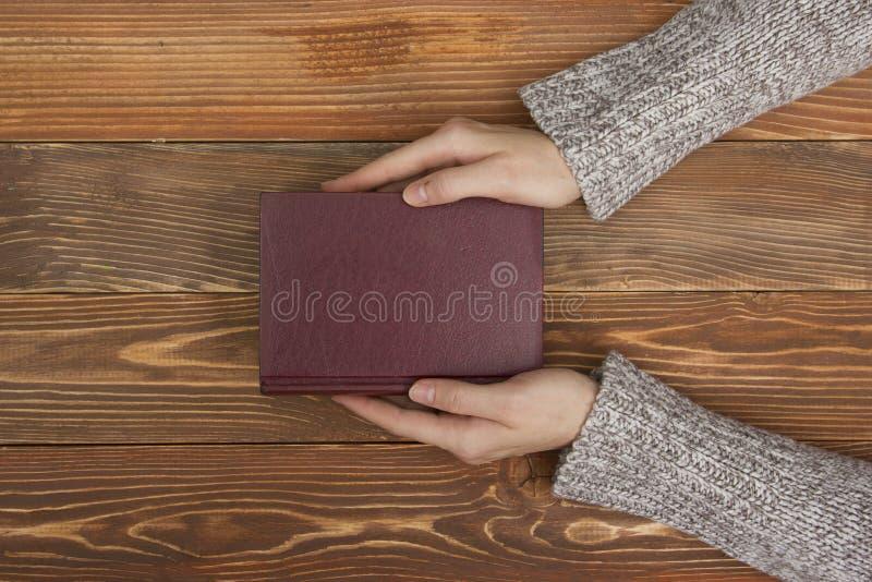女性手拿着空白的空的书或笔记,在木书桌桌上的日志盖子,顶视图 免版税图库摄影