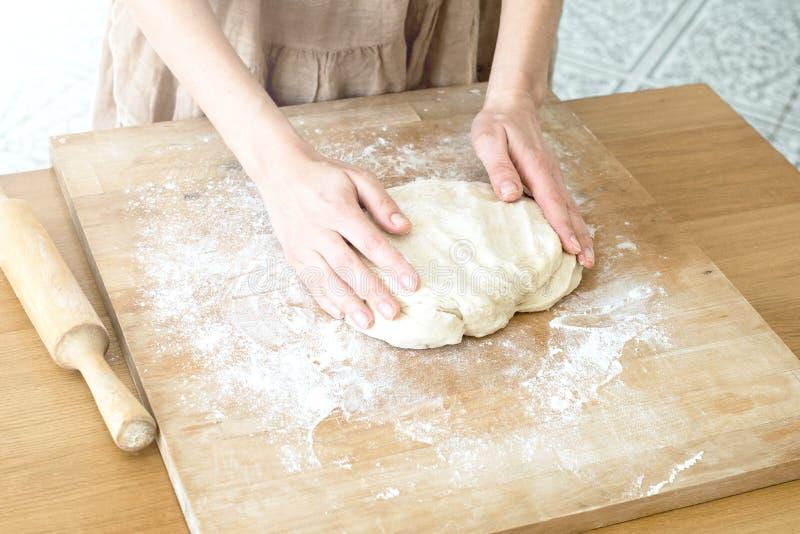 女性手揉在烹调烘烤的一个木板的面团 图库摄影