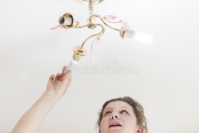 女性手插入一个电灯泡入穿线的插口 她发光 玉米类型家庭LED灯的设施, 免版税库存图片