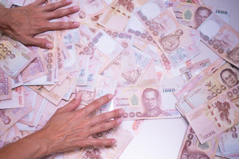 女性手收在一张白色桌,泰国钞票上的很多金钱 库存图片