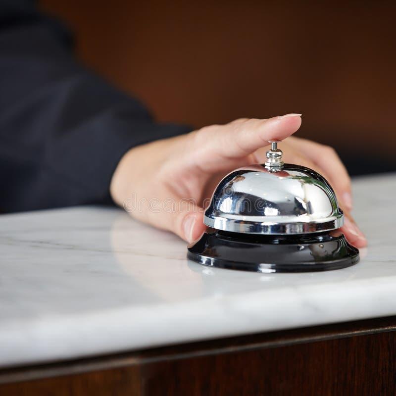 女性手敲响的旅馆响铃 免版税图库摄影
