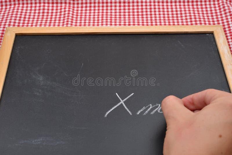 女性手文字,圣诞节蒂姆的特写镜头在黑板的 免版税库存图片