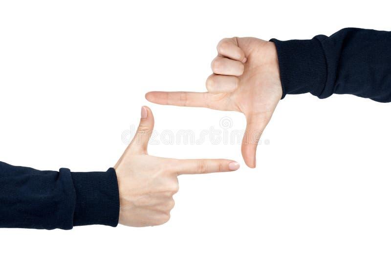 女性手显示与手指姿态和标志的框架 背景查出的白色 深蓝套头衫 免版税库存图片