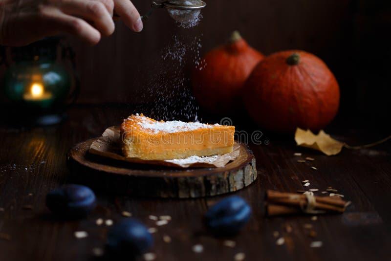 女性手洒在南瓜乳酪蛋糕的搽粉的糖 南瓜,台灯,叶子,在木黑暗的香草 库存照片