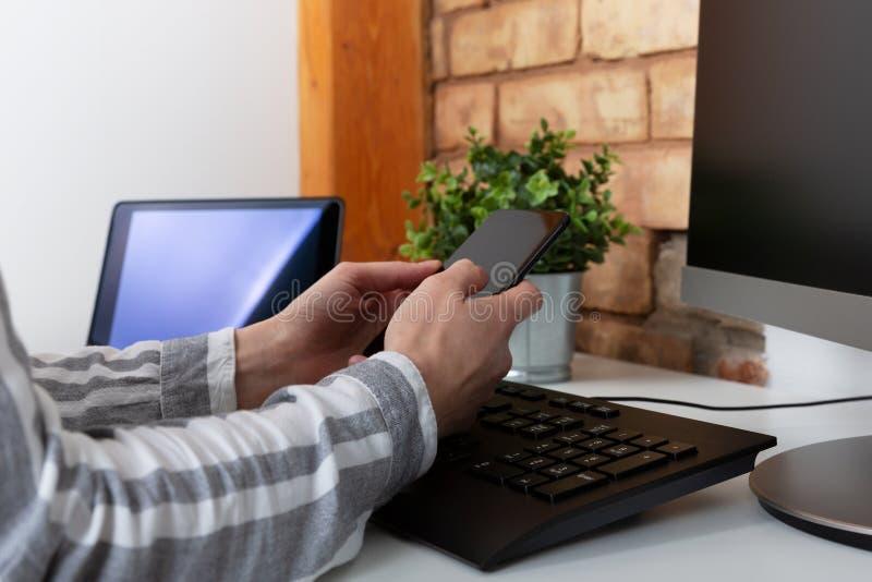 女性手特写镜头使用现代智能手机的,当工作在有计算机的,在她时的女实业家键入的短信办公室 免版税库存照片