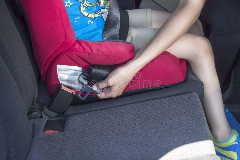 女性手紧固安全带 孩子在汽车座位坐 库存图片