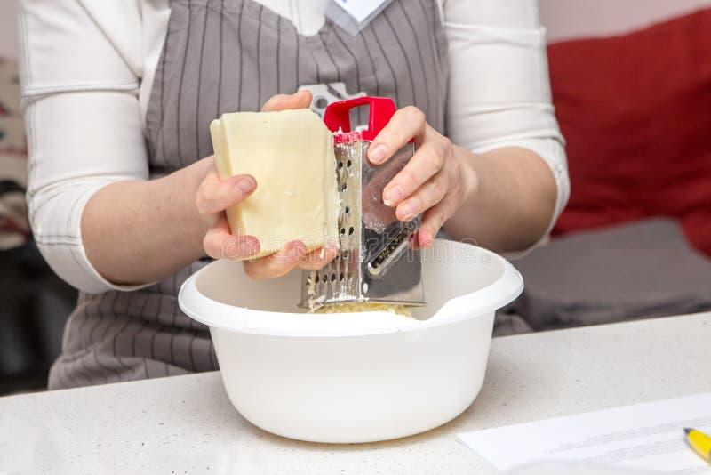 女性手细节磨碎乳酪 妇女乳酪在厨房里为比萨或饼做准备 E 免版税库存照片