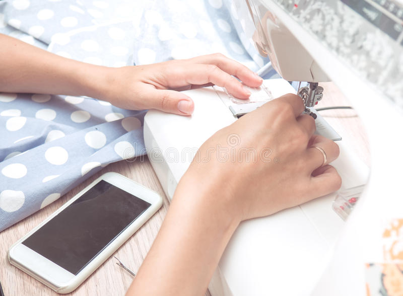 女性手缝合蓝色织品 库存照片